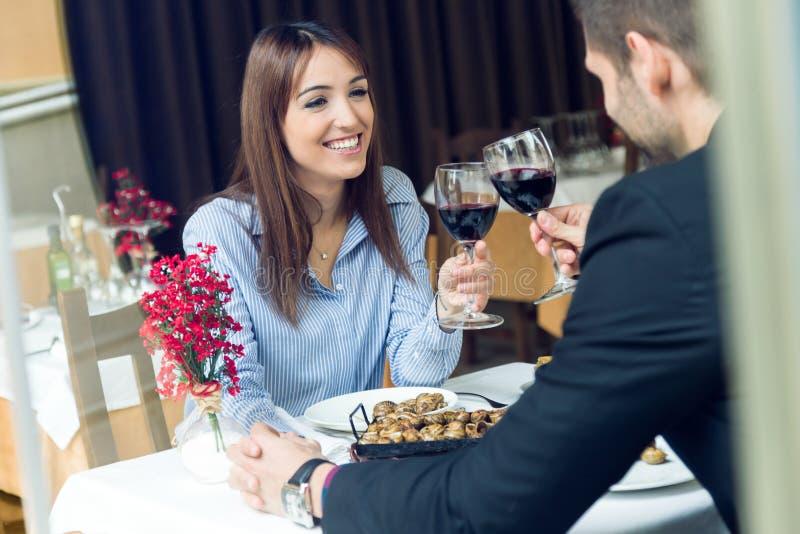 De mooie jonge glazen van de paar roosterende wijn in het restaurant stock foto