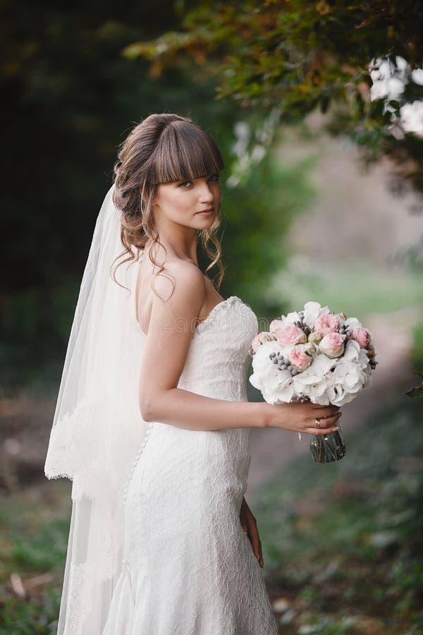 de mooie jonge glimlachende bruid houdt groot huwelijksboeket met roze rozen Huwelijk in rooskleurige en groene tonen De dag van  stock afbeelding