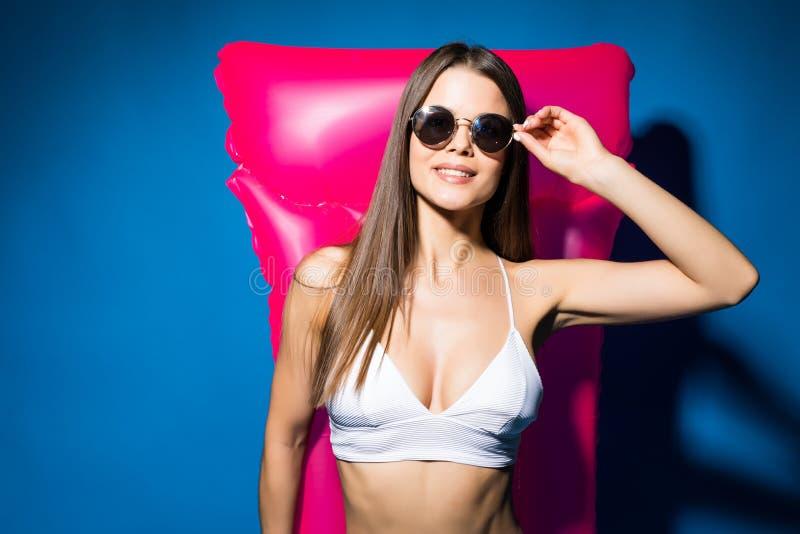 De mooie jonge glimlachende vrouw kleedde zich in witte zwempak en glazen die met roze opblaasbare die matras stellen over blauwe royalty-vrije stock foto