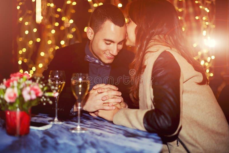 De mooie jonge handen van de paarholding op een romantisch diner in een restaurant stock afbeelding