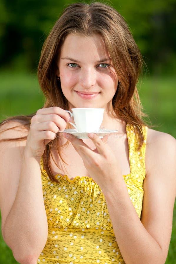 De mooie jonge hete koffie van de vrouwendrank openlucht stock afbeeldingen