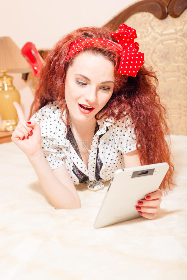 De mooie jonge lezing van de roodharigevrouw met tablet stock foto