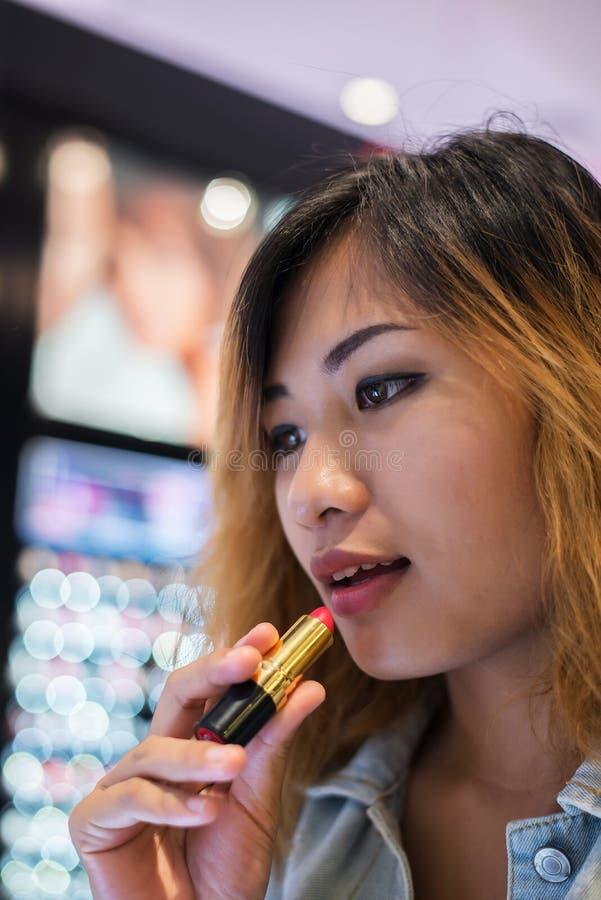 De mooie jonge lippenstift van de vrouwen uitgezochte kleur aan het kopen bij het winkelen stock afbeelding
