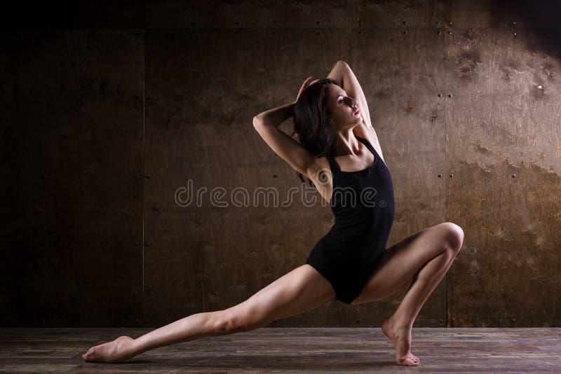 De mooie jonge meisjesdanser met lang stromend haar in zwarte kleren, een gymnastiek- zwempak, in een dans stelt op een houten vl stock foto