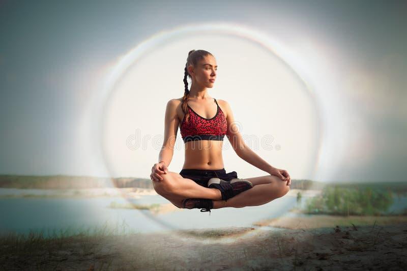 De mooie jonge meisjessportvrouw levitatie ondergaat in lotusbloempositie inzake aard dichtbij meer stock afbeeldingen