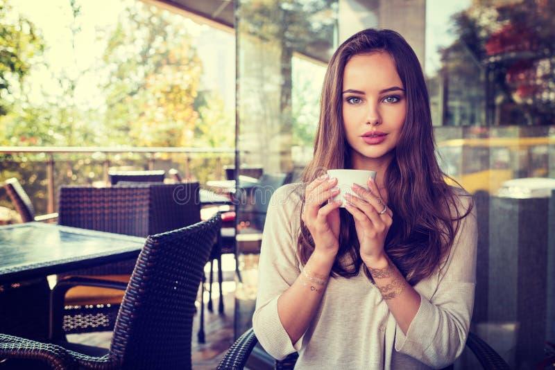 De mooie jonge meisjeszitting alleen in een koffie drinkt koffie stock afbeeldingen