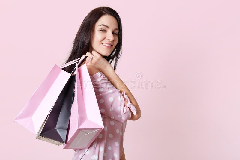 De mooie jonge modieuze vrouw met het winkelen zwarte en rooskleurige zakken, draagt roze stipkleding, kijkt satisied bij camera, stock foto's
