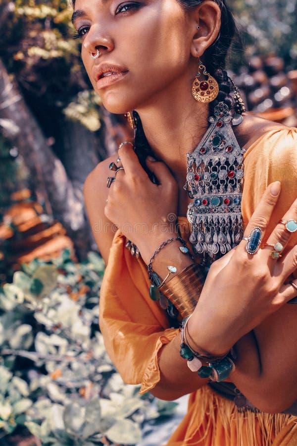 De mooie jonge modieuze vrouw met maakt omhooggaande en modieuze bohotoebehoren stellend op natuurlijke tropische achtergrond royalty-vrije stock fotografie