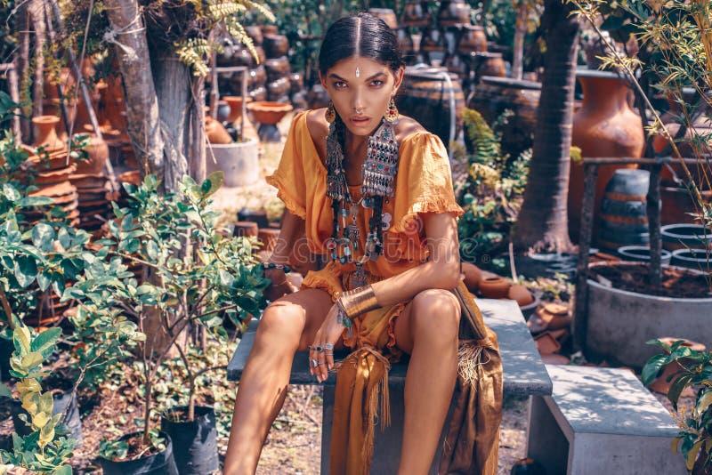 De mooie jonge modieuze vrouw met maakt omhooggaande en modieuze bohotoebehoren stellend op natuurlijke tropische achtergrond royalty-vrije stock foto
