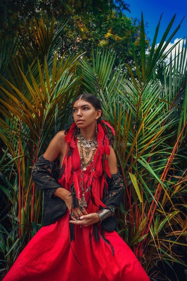 De mooie jonge modieuze vrouw met maakt omhooggaande en modieuze bohotoebehoren stellend op natuurlijke tropische achtergrond stock afbeelding