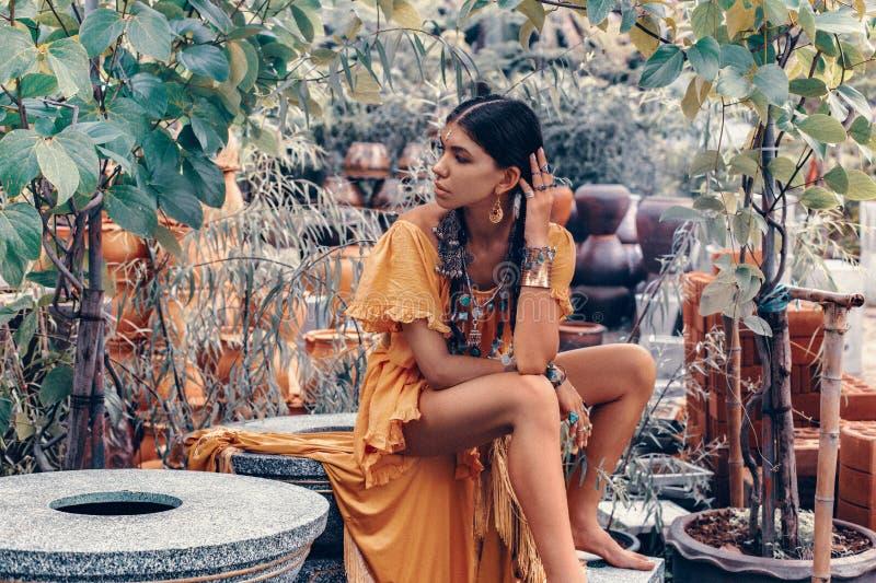 De mooie jonge modieuze vrouw met maakt omhooggaande en modieuze bohotoebehoren stellend op natuurlijke tropische achtergrond stock foto's