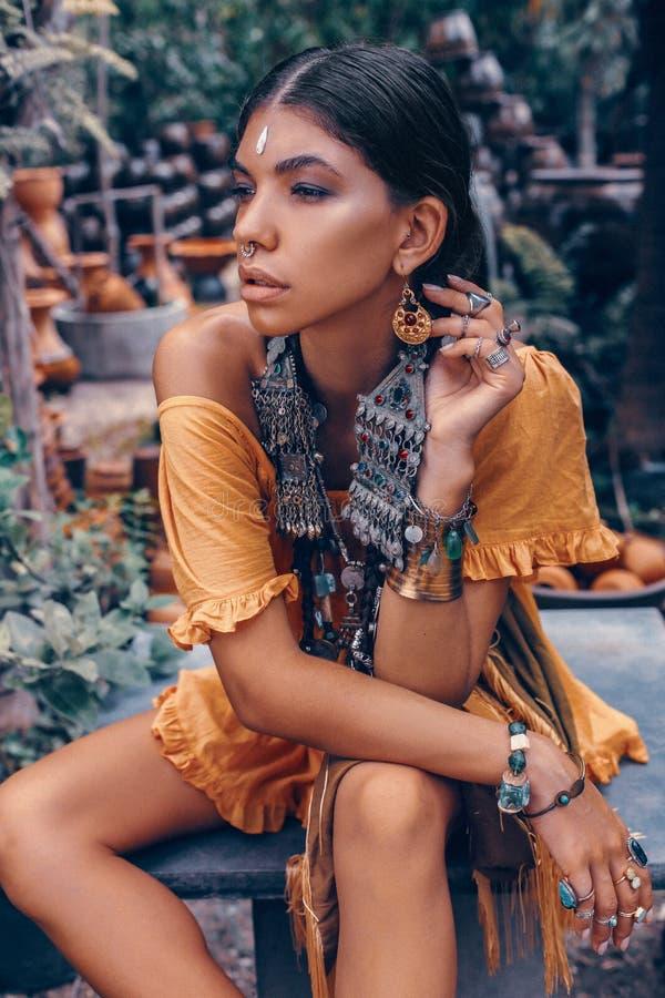 De mooie jonge modieuze vrouw met maakt omhooggaande en modieuze bohotoebehoren stellend op tropische achtergrond stock fotografie