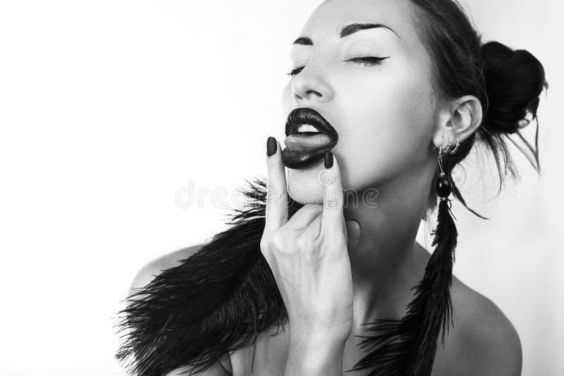 De mooie jonge modieuze vrouw plakt uit haar tong (de Brutale jeugd stock afbeelding