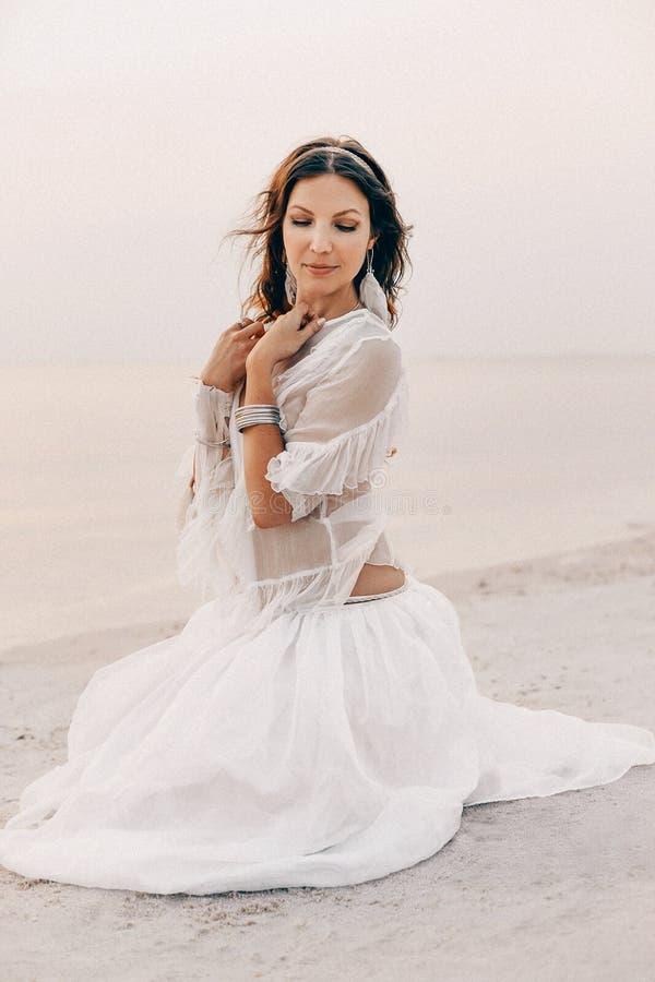 De mooie jonge modieuze zitting van de bohovrouw op het strand bij sunse royalty-vrije stock afbeeldingen