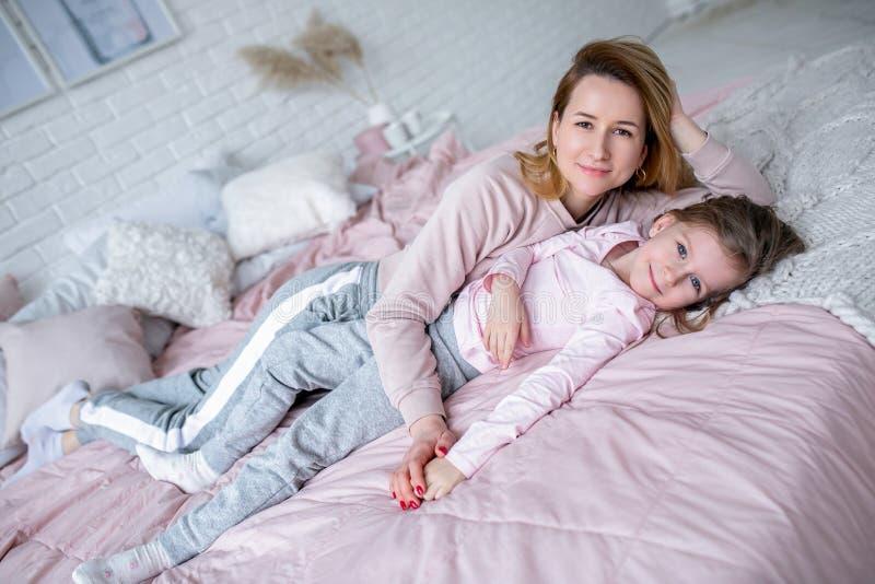 De mooie jonge moeder en haar weinig dochter liggen samen op het bed in de slaapkamer, spelen, koesteren en hebben pret stock foto