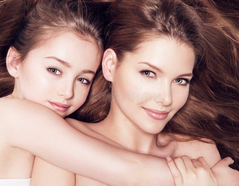 De mooie jonge moeder met een kleine dochter 8 jaar omhelst ea royalty-vrije stock afbeelding