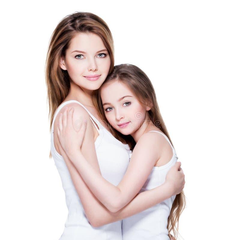 De mooie jonge moeder met een kleine dochter 8 jaar omhelst eac stock foto