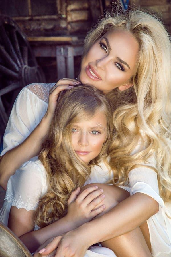 De mooie jonge moeder met haar dochter kleedde zich in de lentekleren en kronen van bloemen royalty-vrije stock afbeelding