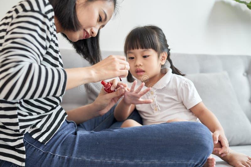 De mooie jonge moeder schildert de spijkervernis aan haar leuke kleine dochter royalty-vrije stock afbeeldingen