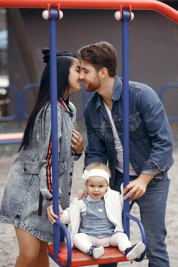 De mooie jonge ouders, gang met een kind, slingeren hem op een schommeling, hebben pret en genieten van elkaar, gelukkige familie stock foto's