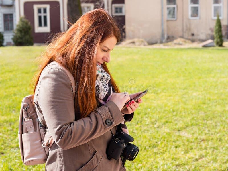 De mooie jonge roodharigevrouw ziet een smartphone in park royalty-vrije stock afbeeldingen