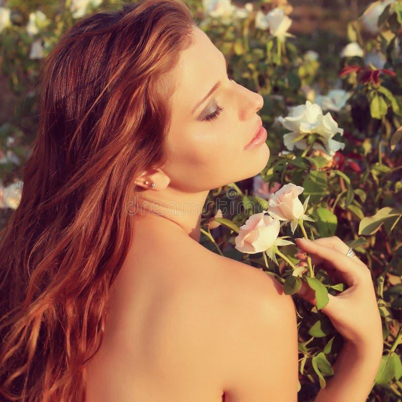 De mooie jonge sensuele vrouw kijkt in de tuin in de zomer. uitstekende foto stock afbeelding