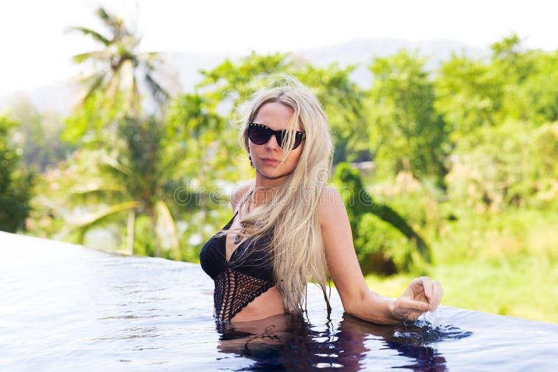 De mooie jonge slanke blondevrouw krijgt bruine kleur dichtbijgelegen zwembad stock fotografie