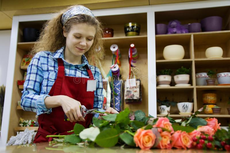 De mooie jonge smilling vrouwenbloemist snijdt de rozen in bloemwinkel royalty-vrije stock afbeeldingen
