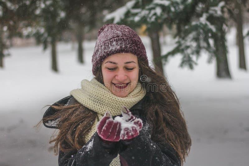 De mooie jonge sneeuw van de vrouwenholding in vuisthandschoenen en het lachen stock afbeelding