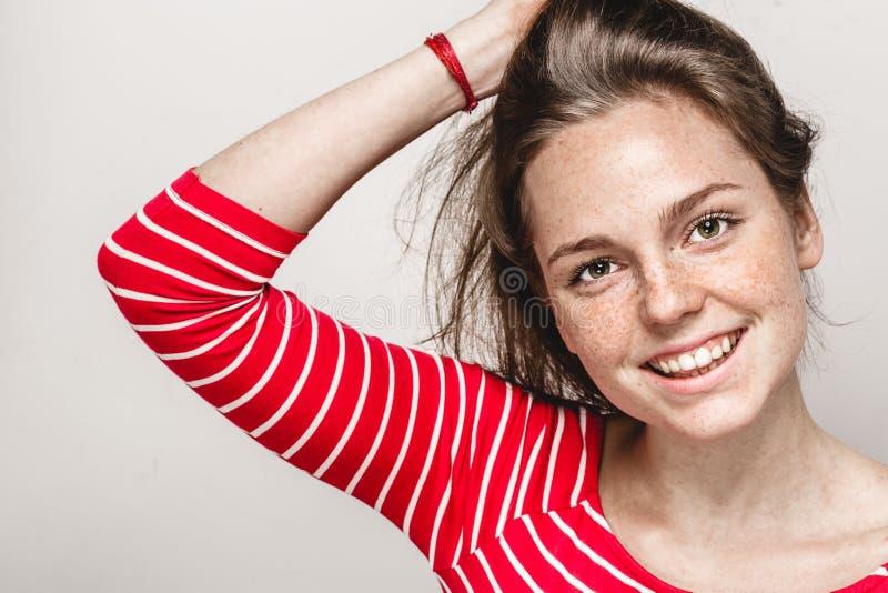 De mooie jonge sproeten die van het vrouwenportret het stellen aantrekkelijk brunette glimlachen royalty-vrije stock afbeeldingen