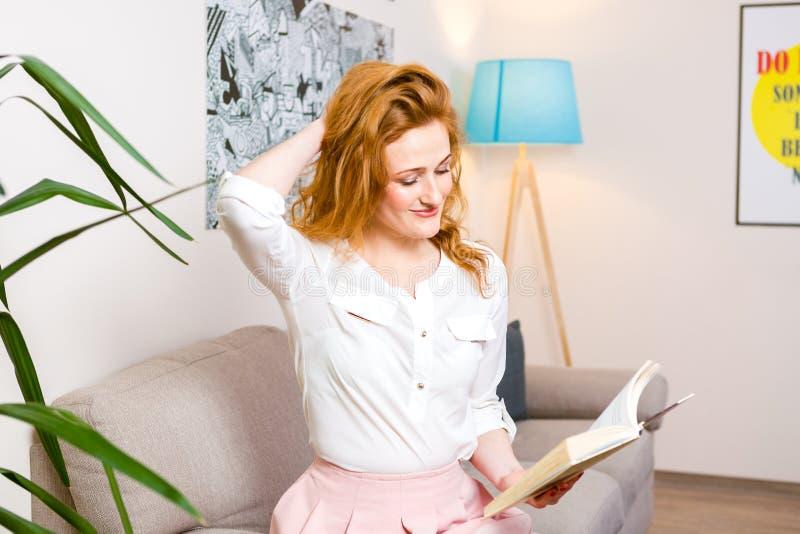 De mooie jonge studente met lang rood haar in roze rok en overhemdslezing boekt, zitting van het holdings in hand handboek op ban stock afbeeldingen