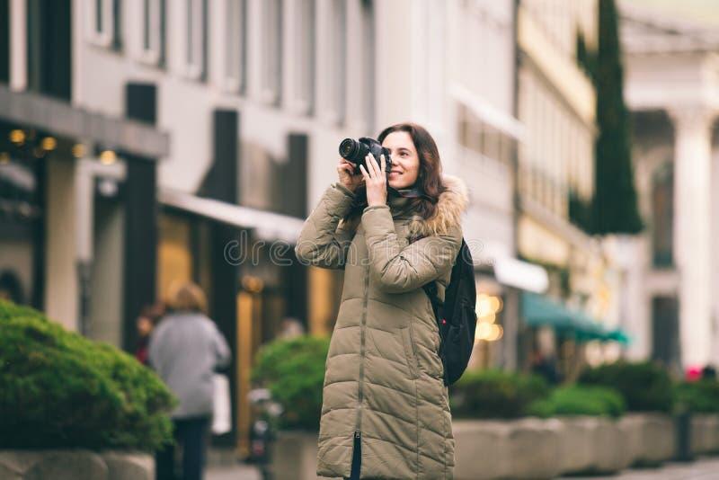 De mooie jonge toeristenvrouw bevindt zich op de achtergrond van de centrale straat in München in Duitsland in de winter Houdt zw stock foto