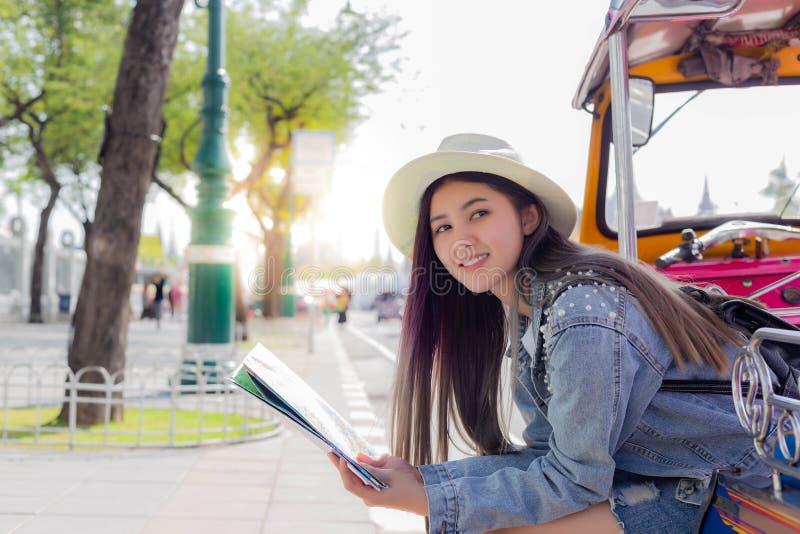 De mooie jonge toeristenvrouw die een rust op tuk nemen tuk taxi?t en wat toeristische attractie op kaart vinden royalty-vrije stock fotografie