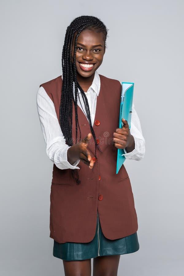 De mooie jonge van Bedrijfs afro Amerikaanse vrouw in formele slijtage houdt een omslag, bekijkt camera en glimlacht op grijze ac royalty-vrije stock foto