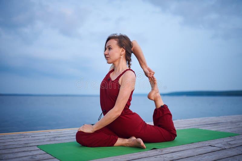 De mooie jonge van de yogaasana van vrouwenpraktijken Koning Pigeon stelt rajakapotasana op het houten dek dichtbij het meer royalty-vrije stock afbeeldingen