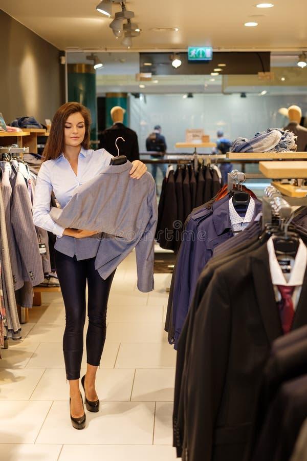 De mooie jonge verkoopster helpt de klant om een jasje in kostuumwinkel te kiezen stock afbeeldingen