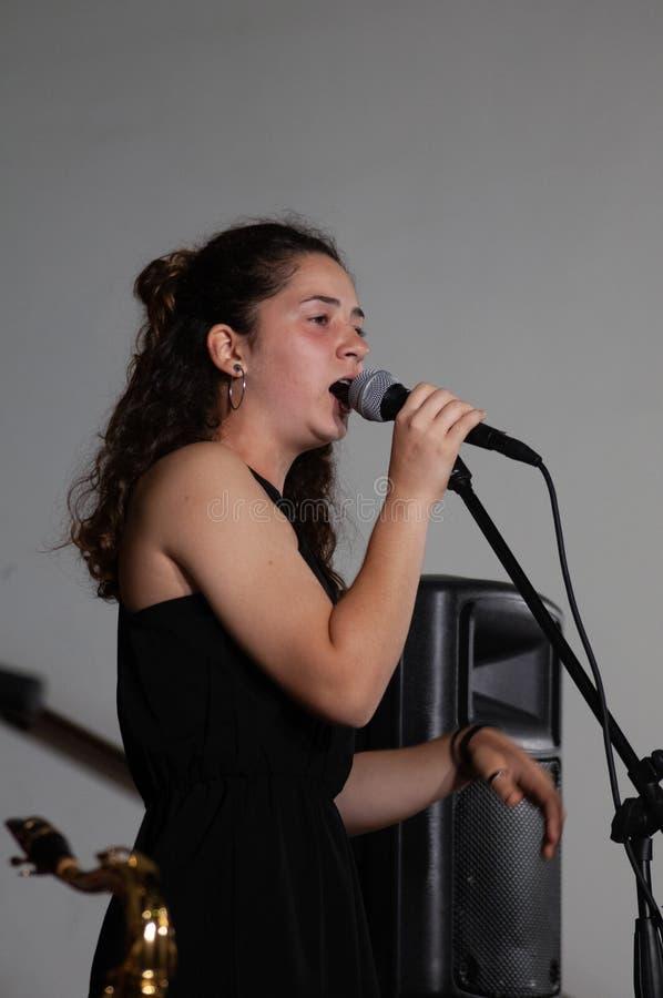 De mooie jonge vocalist donkerbruine zanger, tijdens levend toont met microfoon, met elegante zwarte kleding royalty-vrije stock afbeeldingen