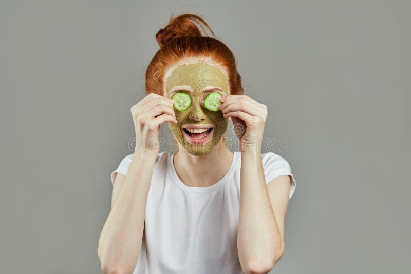 De mooie jonge vrolijke roodharige vrouw krijgt gezichtskleimasker bij kuuroord stock afbeelding