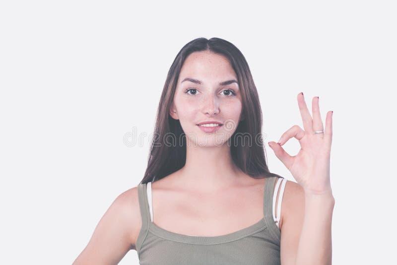 De mooie jonge vrouw bekijkt camera, het tonen van O.k. teken en het glimlachen, zich bevindt tegen grijze muur royalty-vrije stock foto's