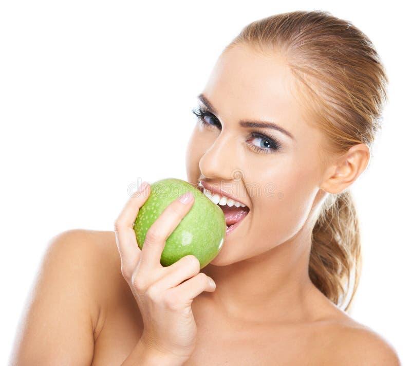 De mooie jonge vrouw bijt een groene appel stock afbeelding