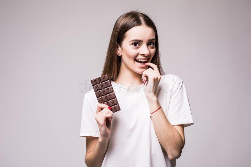 De mooie jonge vrouw die een bar van melkachtige chocolade playfull blik bijten op camera vóór eet geïsoleerd op grijs Het concep royalty-vrije stock foto