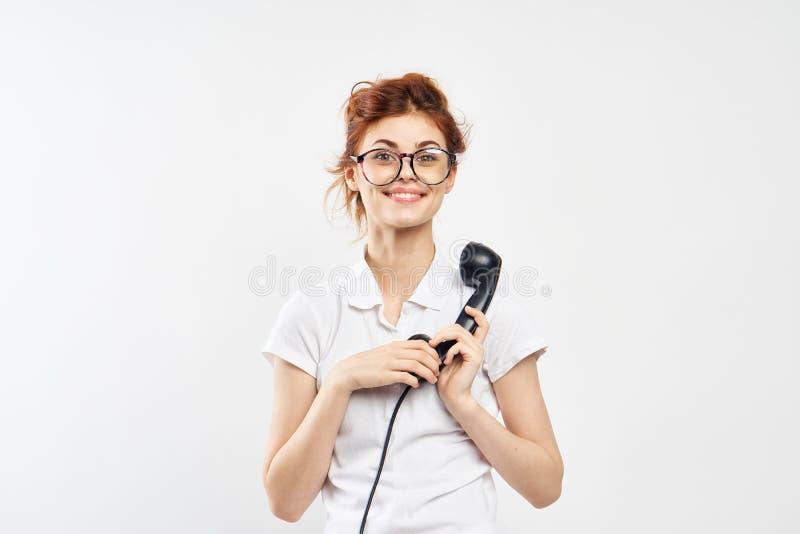 De mooie jonge vrouw die een landline telefoon in glazen op wit houden isoleerde achtergrond, mededeling stock fotografie
