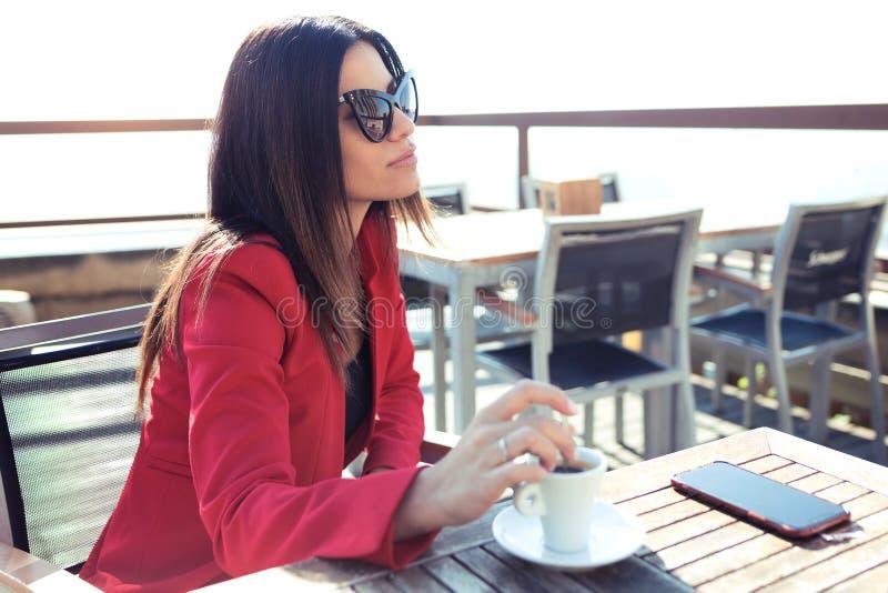 De mooie jonge vrouw die de groene thee van Matcha drinken latte wodden lijst in de koffiewinkel stock afbeelding