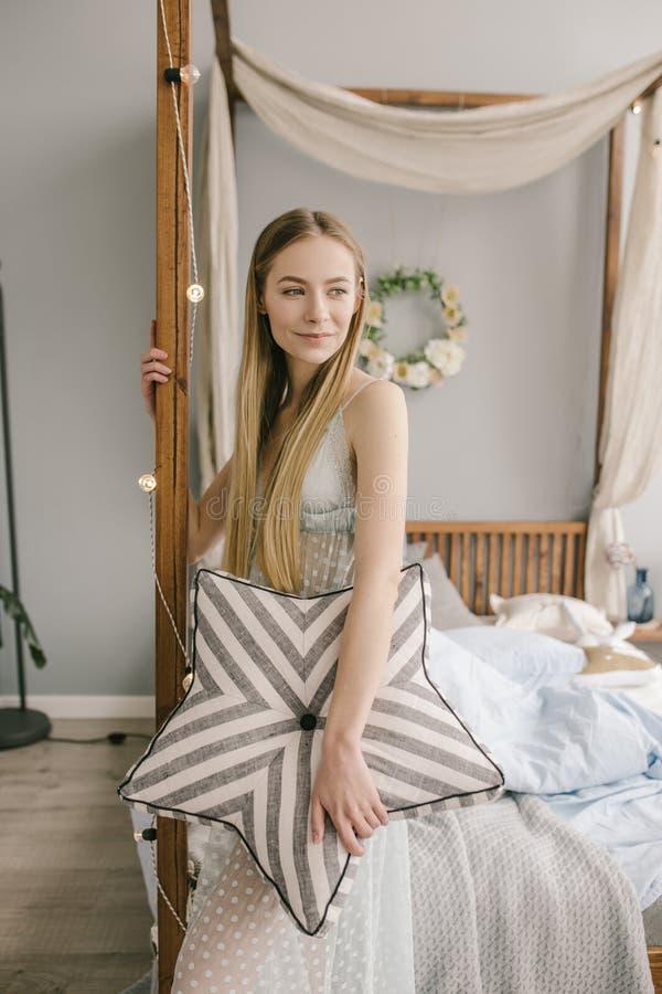 De mooie jonge vrouw die pyjama's in bed dragen houdt thuis een hoofdkussen stock afbeelding