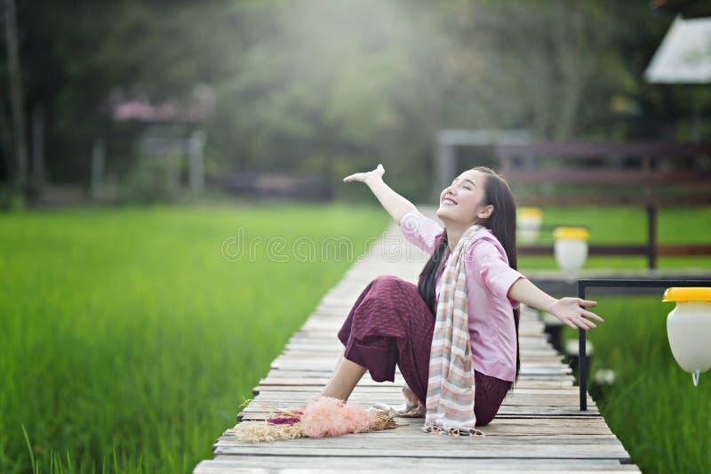 De mooie jonge vrouw die van Laos lokale kledingszitting op houten brug in groen padieveld gelukkig draagt stock foto's