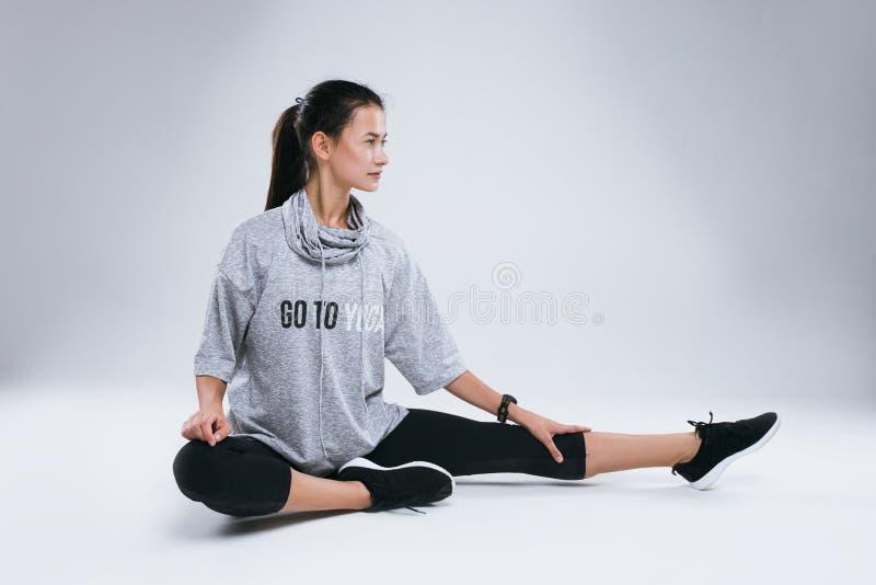 De mooie jonge vrouw die yoga doen oefent terwijl het zitten op de witte achtergrond in studio uit royalty-vrije stock afbeelding