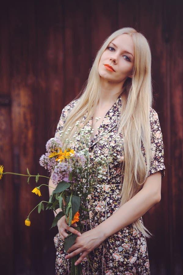 De mooie jonge vrouw doted binnen de zomerkleding op rode oude houten achtergrond, bekijkend camera rustieke stijl, mooi met wild stock foto's