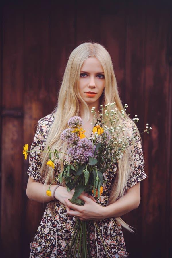 De mooie jonge vrouw doted binnen de zomerkleding op rode oude houten achtergrond, bekijkend camera rustieke stijl, mooi met wild stock afbeelding