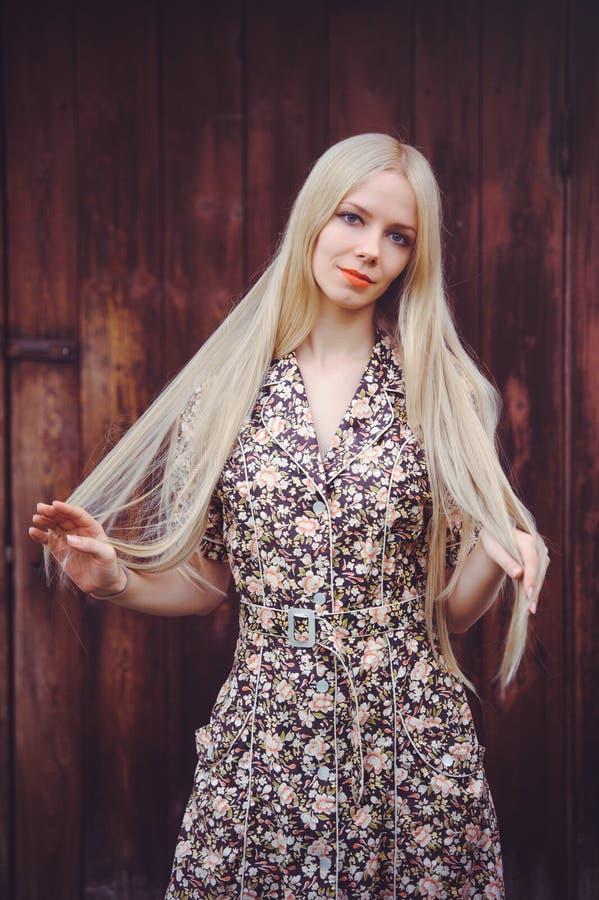 De mooie jonge vrouw doted binnen de zomerkleding op rode oude houten achtergrond, bekijkend camera rustieke stijl, vrij royalty-vrije stock fotografie