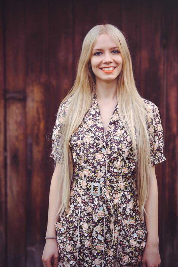 De mooie jonge vrouw doted binnen de zomerkleding op rode oude houten achtergrond, bekijkend camera rustieke stijl, vrij stock foto's